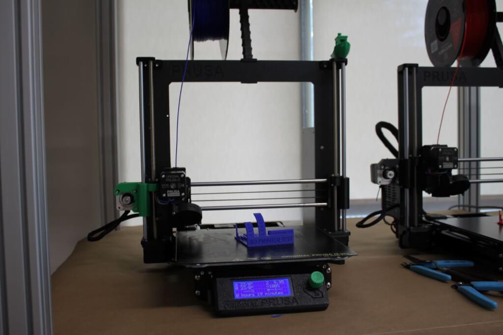 Prusa 3D printer on shelf.