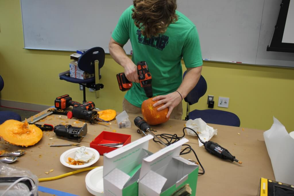 Student etching designs on pumpkin