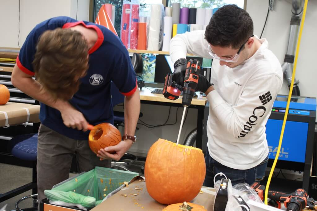 Students extract the insides of pumpkin
