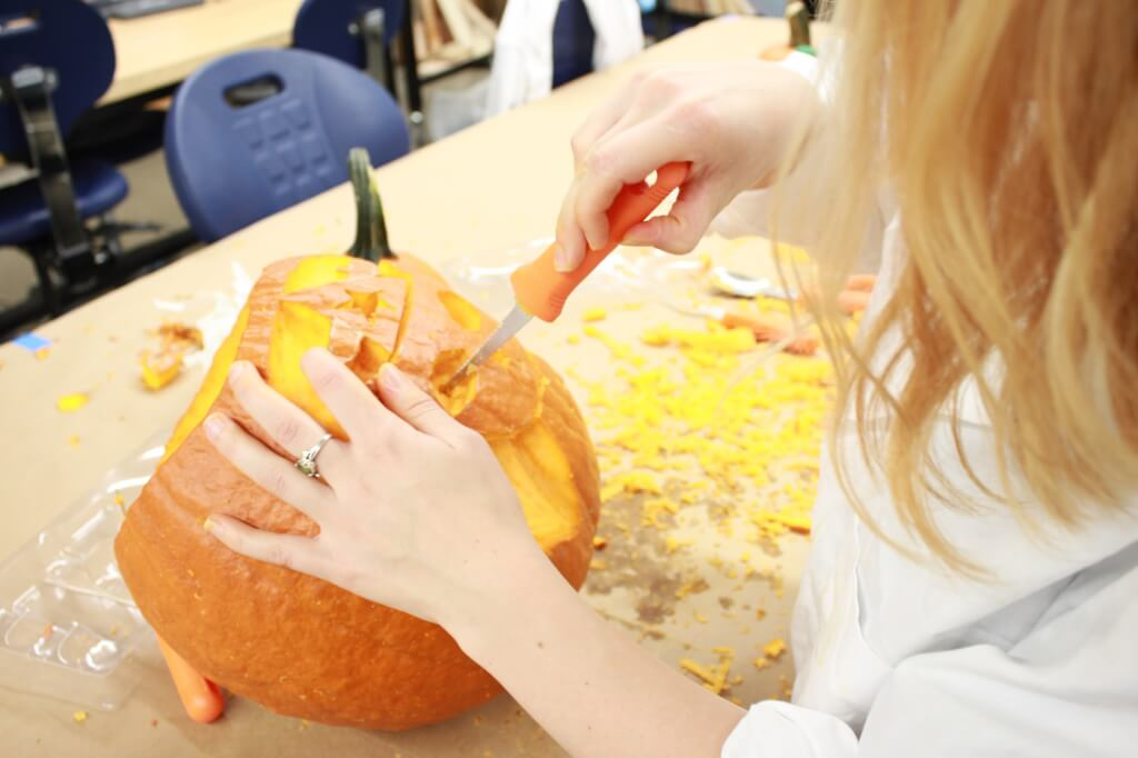 Student carving design into pumpkin