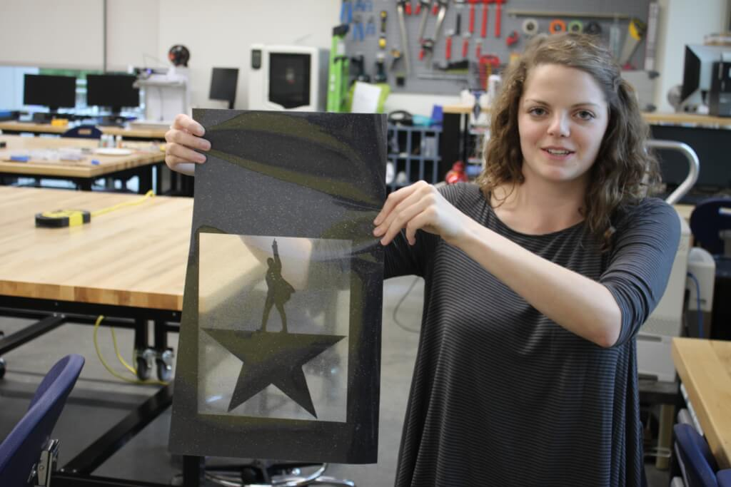 Abbie Callahan holds up the design cut from Black Sparkly Vinyl